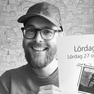 Närbild på en glad Gustaf Lord som håller upp en plansch
